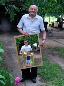 Rüstiger Senior zeigt Bild von Kind und Enkel